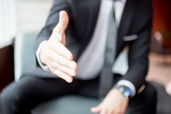 Cropped view of business man sitting and extending arm for handshake with focus on hand